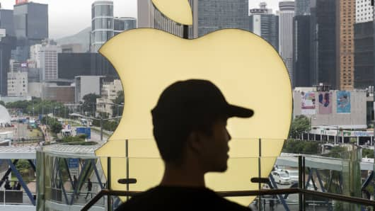 An Apple employee stands in front of an Apple store in Hong Kong.