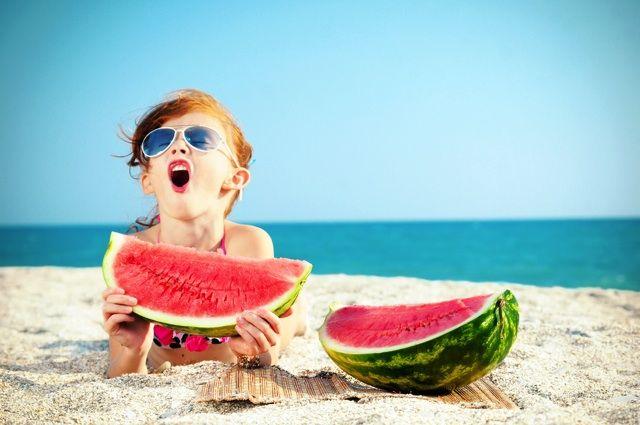 ビーチに寝ころびすいかを食べる外国人少女