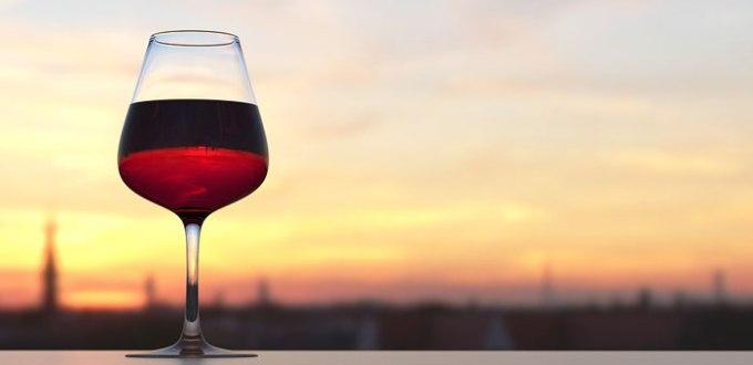 夕暮れの美しい街並みと並んだワイングラスに注がれた赤ワイン