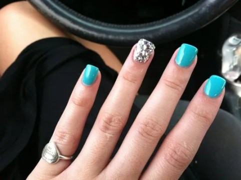 Accentuated turquoise acrylic nails.