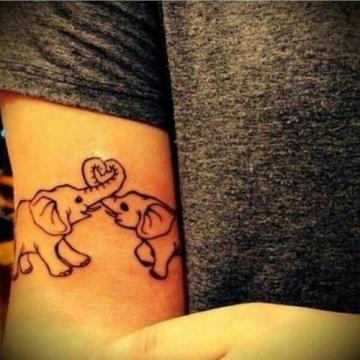 cute elephants making heart with their trunk on the inner arm tattoo