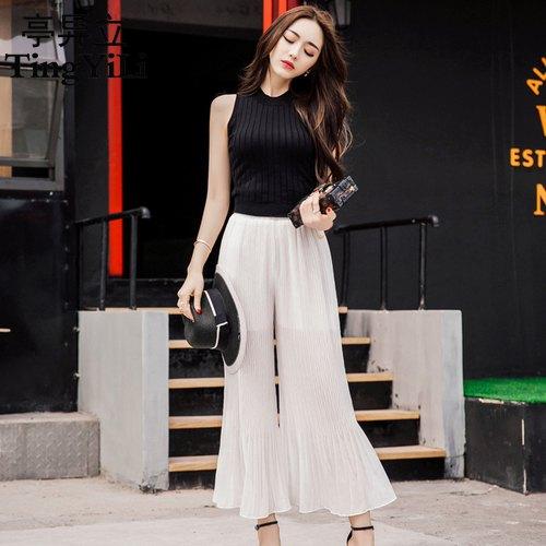 black sleeveless knit sweater white pants
