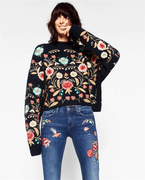all embroidered outfit with black sweater blue jeans