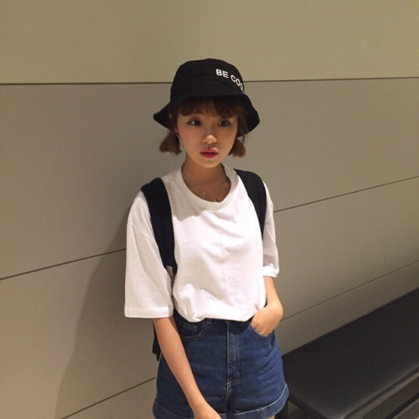 black bucket hat with white oversized tee and denim flowy shorts