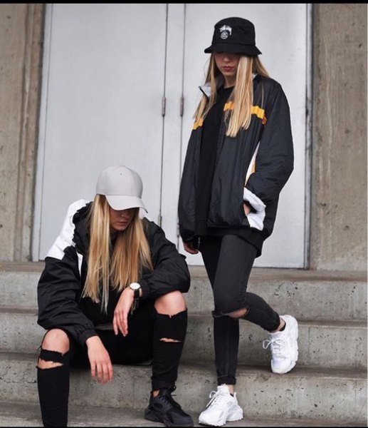 black bucket hat with wind breaker and ripped jeans