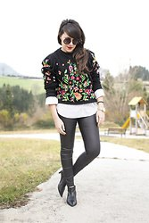 black embroidered sweatshirt with white button up shirt leather leggings