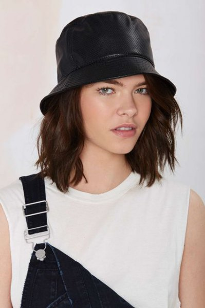 black leather bucket hat with white sleeveless top and denim overall