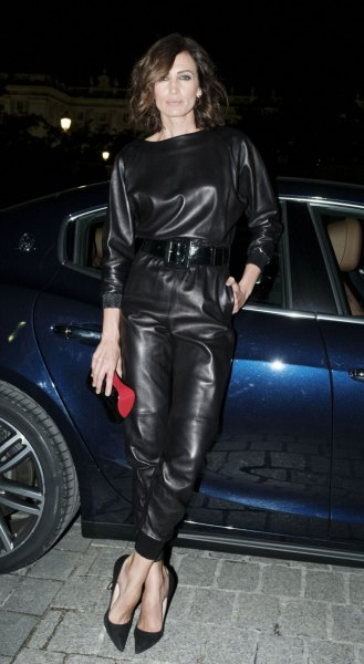 black long sleeve belted leather jumpsuit with red clutch bag