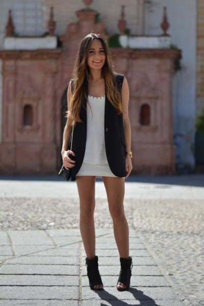 black sleeveless blazer with white mini shift dress