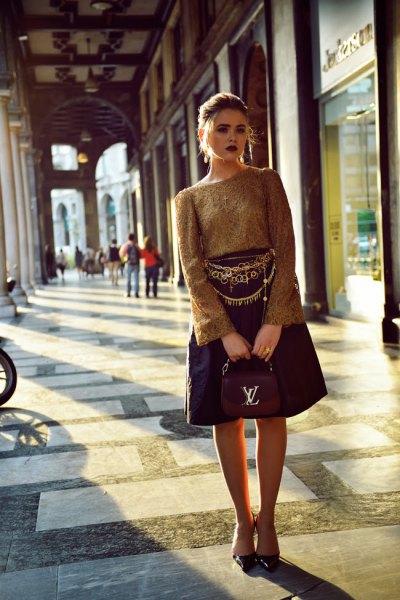 gold belt green bell sleeve top black flared knee length skirt