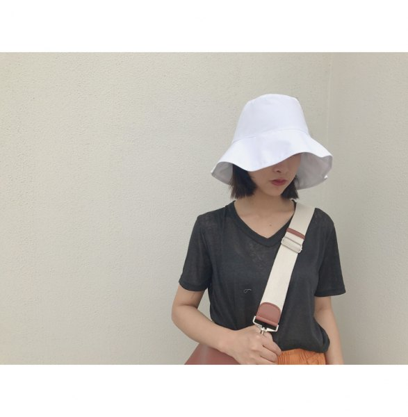 white bucket hat with dark grey tee orange midi flared skirt