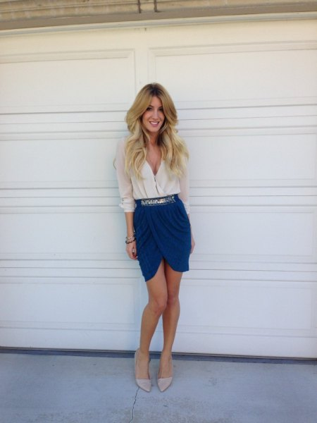 white deep v neck blouse with blue tulip skirt and silver belt