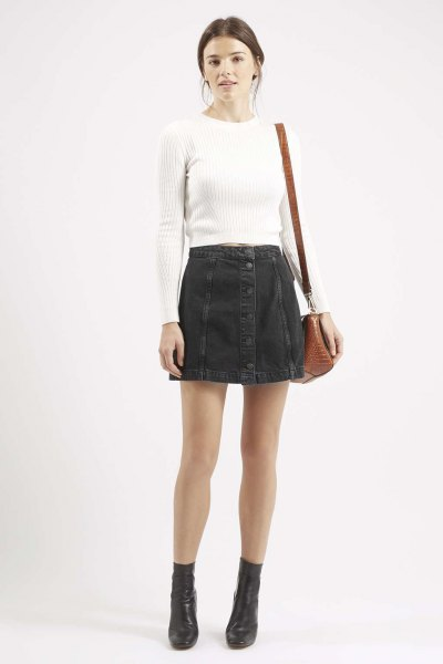 white form fitting ribbed sweater with black button front denim mini skirt