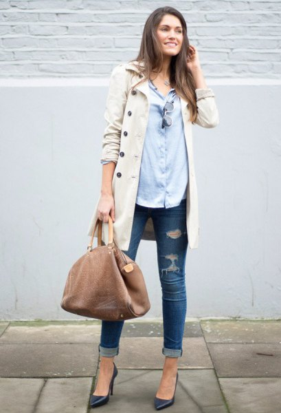 beige long coat with light blue shirt and ripped skinny jeans