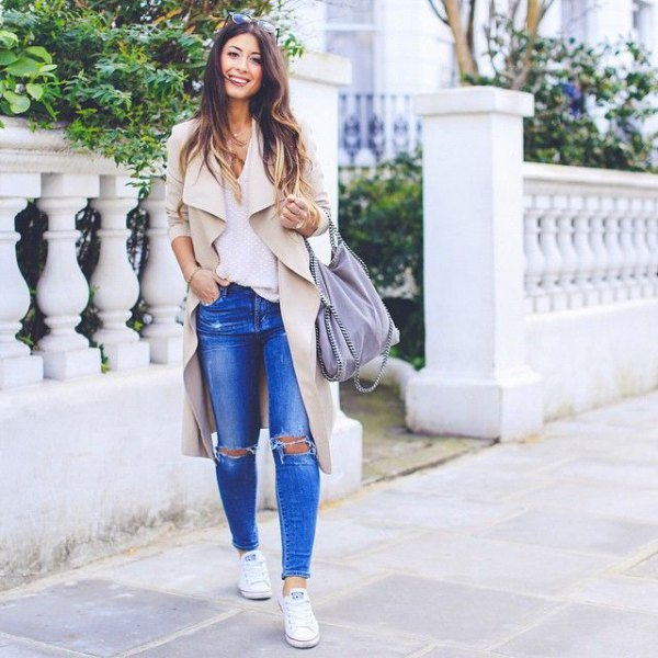 beige trench coat with ripped blue jeans and sneakers