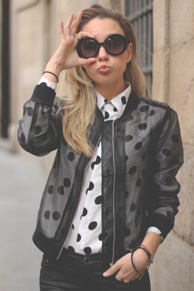 black mesh bomber jacket over white polka dot shirt