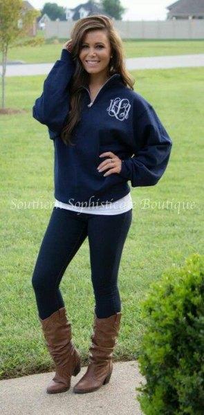 blue half zip hoodie with black leggings and boots