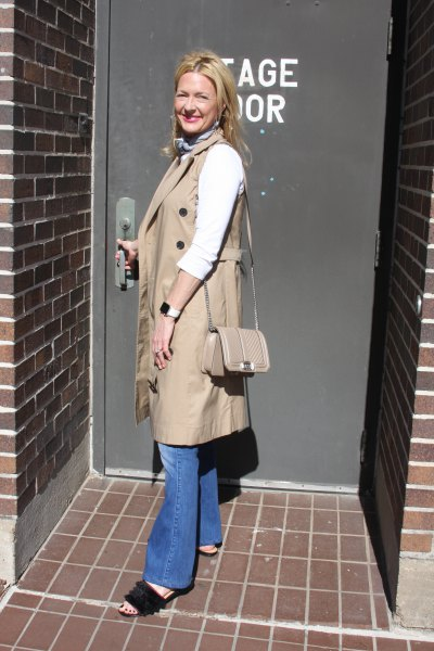 camel sleeveless coat with blue flared jeans