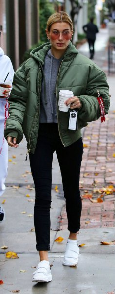 green bubble coat with grey hoodie and black jeans