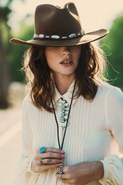 green cowboy hat with white pleated blouse and jeans