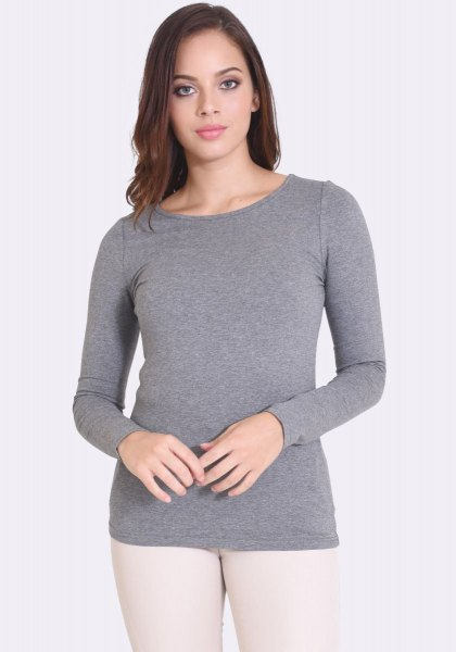 grey form fitting long sleeve top with white skinny jeans
