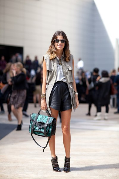 grey sleeveless military jacket with black leather shorts