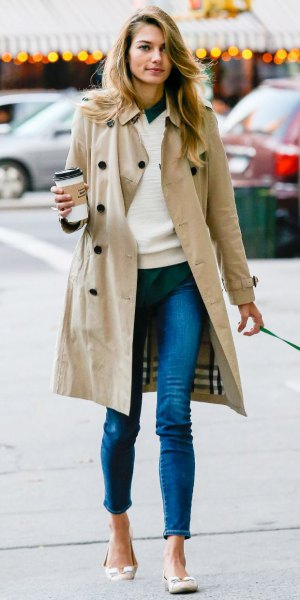 long trench coat with white sweater and blue jeans