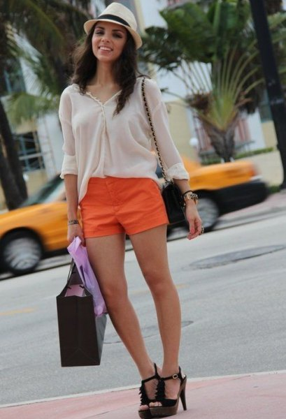 white blouse with straw hat and orange mini shorts