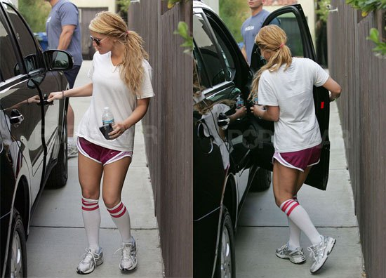 white oversized t shirt with running shorts and knee high socks