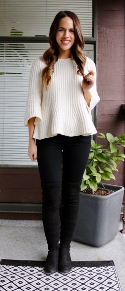white ribbed sweater with black skinny jeans and leather boots