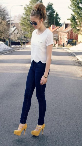 white scalloped t shirt with dark blue jeans and yellow heels