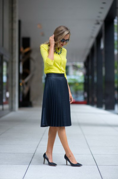 yellow blouse with black high waisted pleated midi skirt
