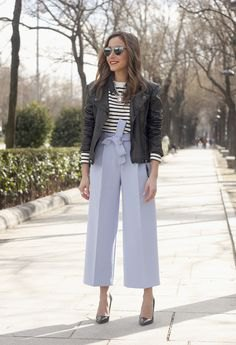black bomber jacket with black and white striped sweater and wide leg blue pants