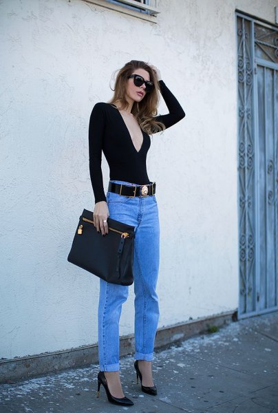 black deep v neck form fitting long sleeve tee with blue jeans and cowboy belt