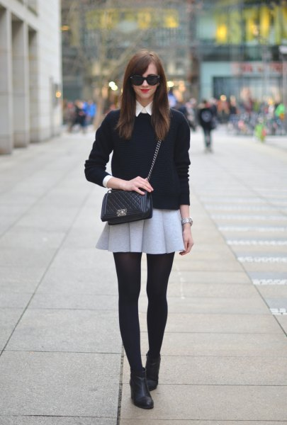 black sweater with light grey mini wool skirt