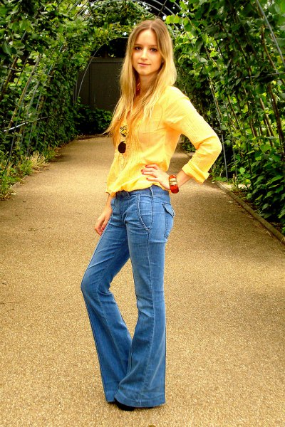 bright yellow long sleeve blouse with blue flared jeans