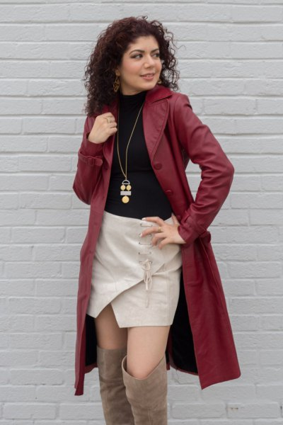brown leather trench coat with black sweater and pink skort