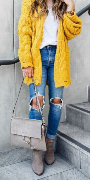 chunky cable knit yellow cardigan with ripped blue jeans