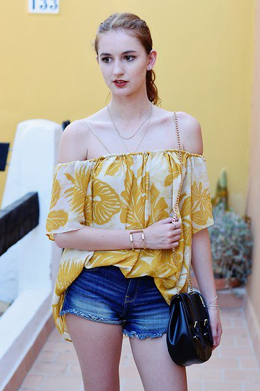 gold and white printed off the shoulder blouse with blue denim shorts