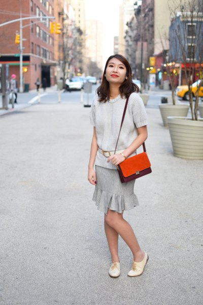 ivory short sleeve sweater with grey ruffle mini skirt and white leather oxford shoes