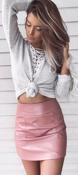light grey knotted knit sweater with pink bodycon mini leather skirt