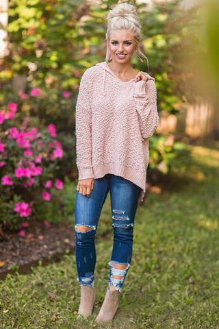pink fuzzy sweater with blue ripped jeans