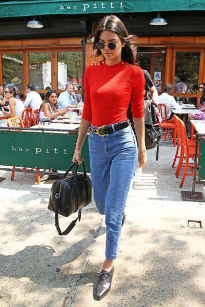 red form fitting sweater with light blue skinny ankle jeans