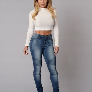 white mock neck cropped form fitting sweater with blue high waisted jeans