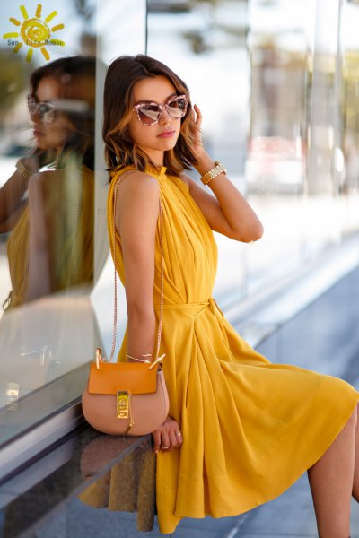 yellow sleeveless pleated midi pleated dress with pink purse