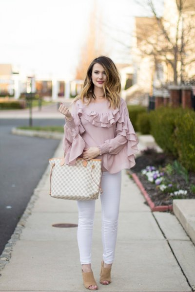 blush pink ruffle sleeve and neck shirt with white skinny jeans