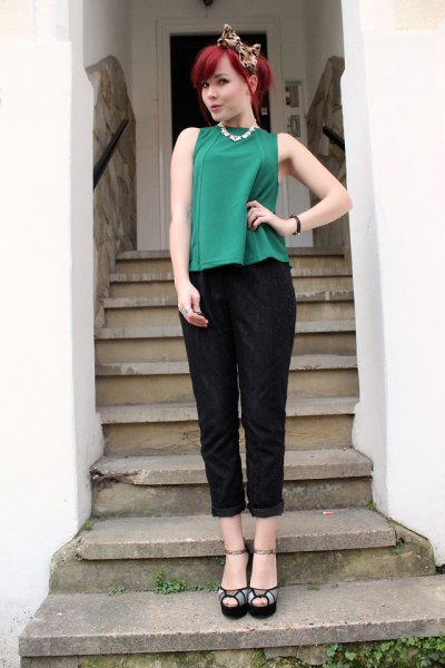 green sleeveless top with black cuffed pants