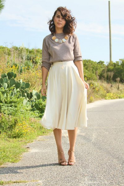 grey sweater with statement necklace with white midi flowy skirt