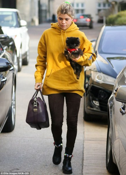 mustard yellow long hoodie with black leggings and ankle boots