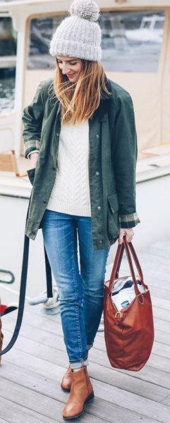 olive green jacket with white cable knit sweater and ankle leather boots